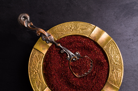 Traditional asian spice sumac in metallic utensil on dark background. Selective focus.
