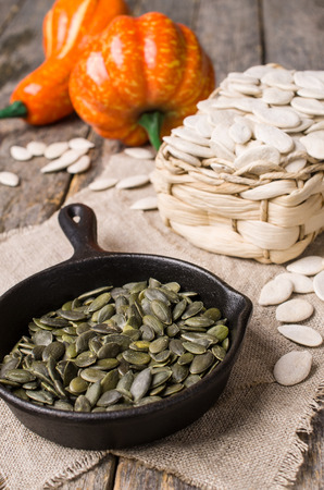 Pumpkin seeds in a pan  on wooden background in rustic style. Selective focus.