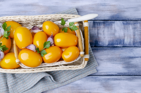 Raw yellow tomatoes with spices on wooden background. Selective focus.