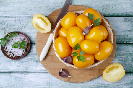 Raw yellow tomatoes with spices on wooden background. Selective focus. Stock Photo - 108614750