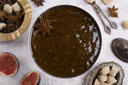 Traditional Fig jam with spices in a metal plate. Selective focus.
