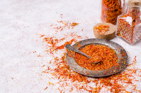 Traditional dry saffron spice on stone background. Selective focus. Imagens