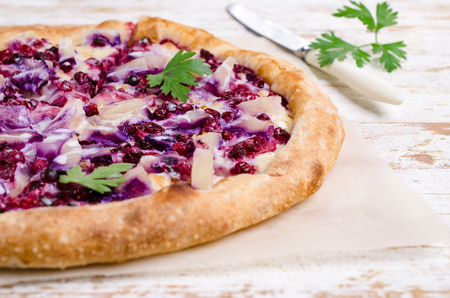 Traditional sweet pizza with berries and pineapple on wooden background. Selective focus.