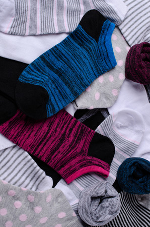Short clean knitted socks scattered in the background. Selective focus.