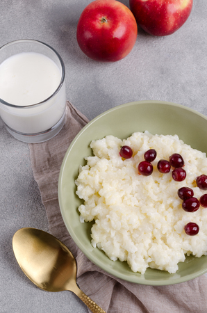 Rice pudding with red berries in a dish on the table. Selective focus. Stock Photo