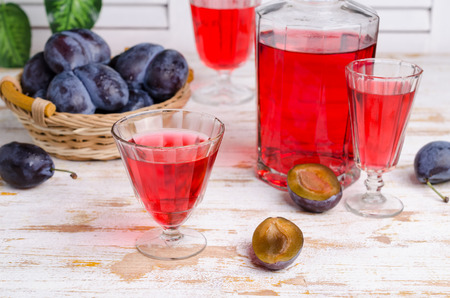Transparent red drink in glass with fresh plums on wooden background. Selective focus. 版權商用圖片
