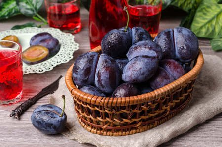 Fresh purple plums with water drops on wooden background. Selective focus. 版權商用圖片