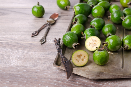 Fresh green feijoa in tableware on wooden background. Selective focus.