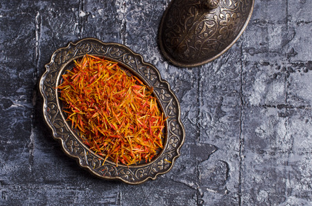 Traditional dry saffron spice on dark slate background. Selective focus.
