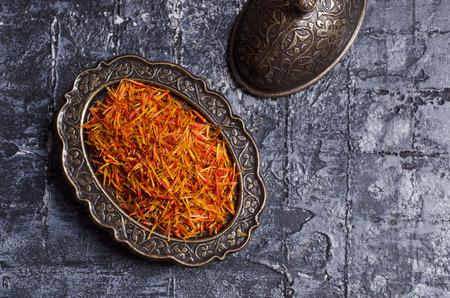 Traditional dry saffron spice on dark slate background. Selective focus. Reklamní fotografie - 112103121