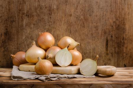 Cebollas orgánicas crudas grandes sobre fondo de madera. Enfoque selectivo.
