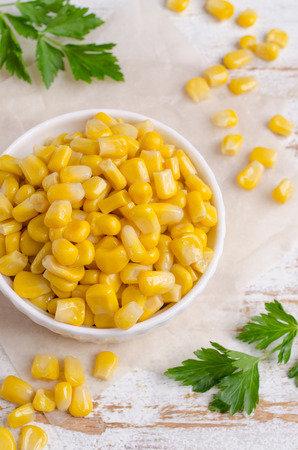 Sweet canned corn in a dish on a wooden background. Selective focus. Stock Photo