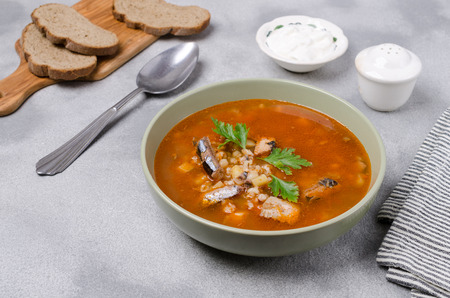 Traditional tomato fish soup with pearl barley and vegetables. Selective focus. Foto de archivo