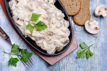 Slices of mushrooms and meat with white sauce on wooden background. Selective focus. Stock Photo