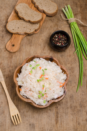 Traditional sauerkraut with carrots and onions on wooden background. Selective focus. Reklamní fotografie