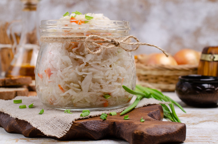 Traditional sauerkraut with carrots and onions on wooden background. Selective focus. Фото со стока