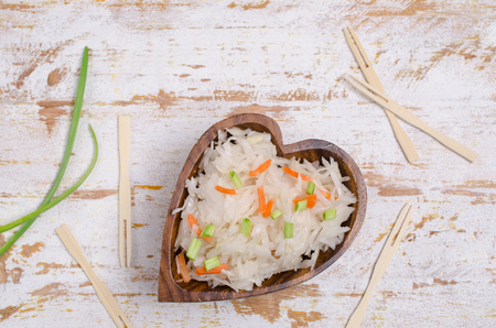 Traditional sauerkraut with carrots and onions on wooden background. Selective focus. Stock Photo