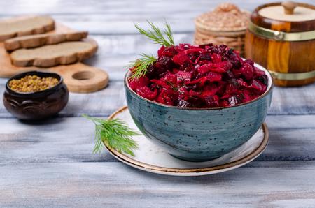 Tradycyjna sałatka z gotowanych warzyw z kiszoną kapustą w misce na drewnianym tle. Selektywne skupienie. Zdjęcie Seryjne