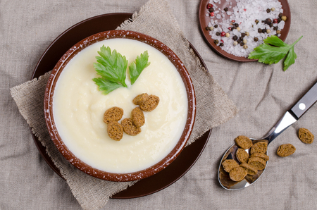 Thick vegetable cream soup with croutons on a textile background. Selective focus.