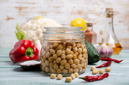 Canned chickpeas in a glass jar on a wooden background. Selective focus.