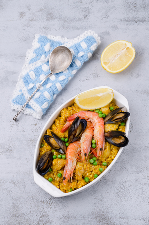 Traditional paella with seafood and meat slices. Selective focus.