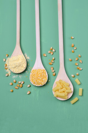 Dry corn products. Grains, polenta, flour, pasta. Green wooden background. Selective focus. Zdjęcie Seryjne