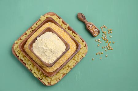 Dry corn products. Grains, polenta, flour, pasta. Green wooden background. Selective focus. 版權商用圖片