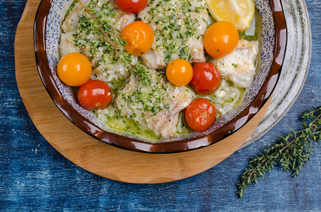 Baked sea fish fillet with vegetables and green sauce on wooden background. Selective focus.