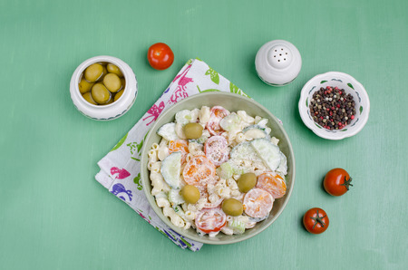 Salad with pasta and raw vegetables in a bowl on a wooden background. Selective focus.