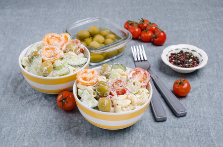 Salad with pasta and raw vegetables in a bowl on a textile background. Selective focus. Archivio Fotografico