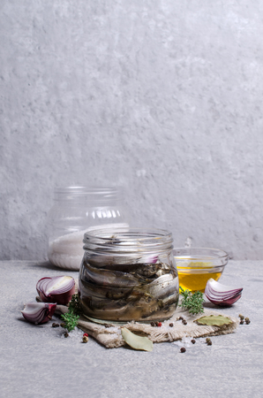 Organic fermented small fish with spices in a glass jar on a grey slate background. Selective focus.