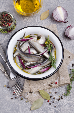 Organic fermented small fish with spices in a metal bowl on a grey slate background. Selective focus.