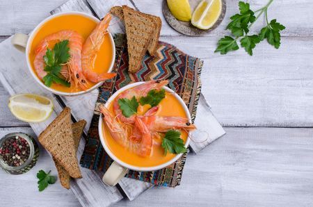 Traditional creamy soup with shrimp and parsley in a bowl on the table. Selective focus. Stock Photo