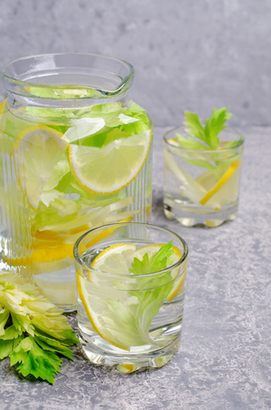 Infused water with lemon and celery in glass on grey background. Selective focus. Reklamní fotografie