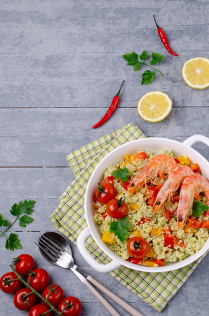 Couscous with vegetables and shrimp in a dish on the table. Selective focus.