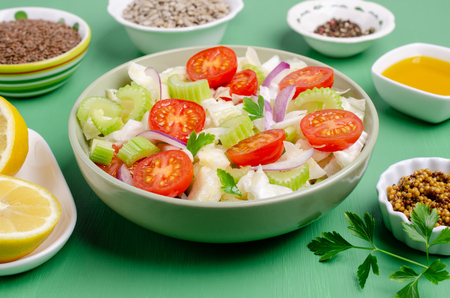 Salad of raw vegetables with seeds in a bowl on a green wooden background. Selective focus. Standard-Bild - 121034502