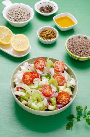 Salad of raw vegetables with seeds in a bowl on a green wooden background. Selective focus. Standard-Bild - 121034503