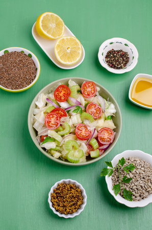 Salad of raw vegetables with seeds in a bowl on a green wooden background. Selective focus. Standard-Bild - 121034505