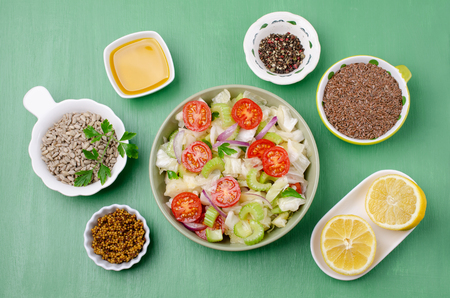 Salad of raw vegetables with seeds in a bowl on a green wooden background. Selective focus. Standard-Bild - 121034506
