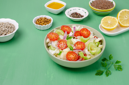 Salad of raw vegetables with seeds in a bowl on a green wooden background. Selective focus. Standard-Bild - 121034513