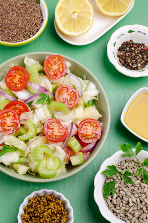Salad of raw vegetables with seeds in a bowl on a green wooden background. Selective focus. Standard-Bild - 121034514