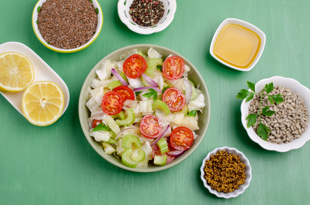 Salad of raw vegetables with seeds in a bowl on a green wooden background. Selective focus. Standard-Bild - 121034515