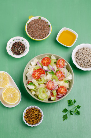 Salad of raw vegetables with seeds in a bowl on a green wooden background. Selective focus. Standard-Bild - 121034516
