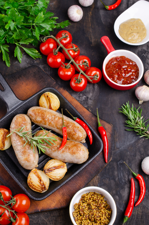 Fried sausages in a pan on a dark background with raw vegetables. Selective focus. Standard-Bild - 121034527