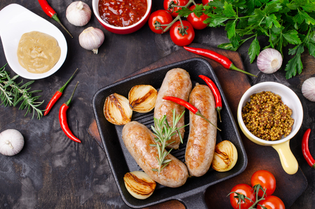 Fried sausages in a pan on a dark background with raw vegetables. Selective focus. Standard-Bild - 121034529