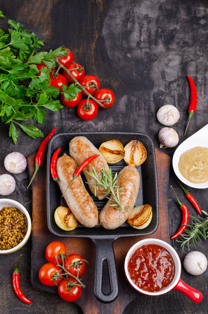 Fried sausages in a pan on a dark background with raw vegetables. Selective focus. Standard-Bild - 121034530
