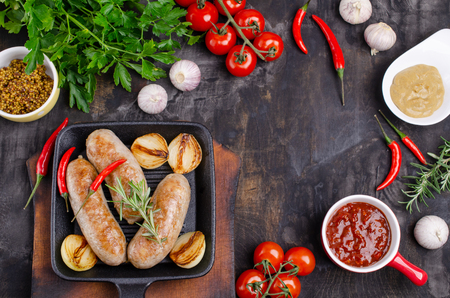 Fried sausages in a pan on a dark background with raw vegetables. Selective focus. Standard-Bild - 121034536