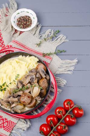 Mashed potatoes and slices of mushrooms with sausages in sauce. Selective focus. Standard-Bild - 121034541