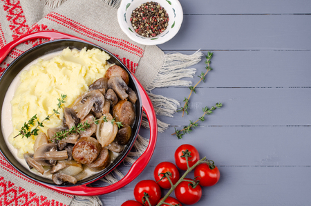 Mashed potatoes and slices of mushrooms with sausages in sauce. Selective focus. Standard-Bild - 121034552
