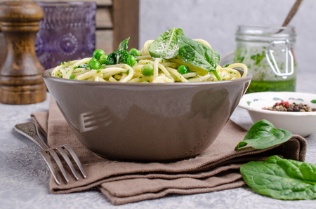 Spaghetti with vegetables, pesto and cheese in a dish on a slate background. Selective focus. Standard-Bild - 121034557